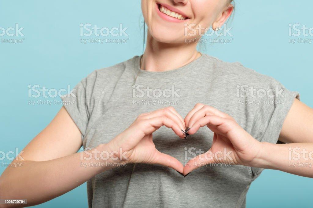 sonriente mujer corazón forma manos amor sentimientos - foto de stock