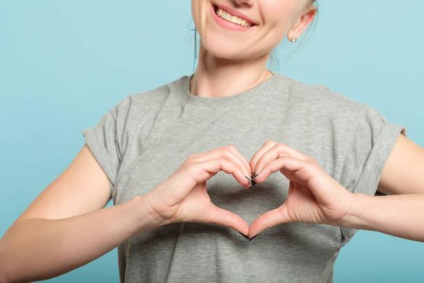 lachende vrouw hart vorm handen hou van gevoelens - bedankt stockfoto's en -beelden