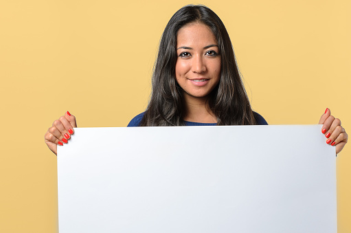 istock Smiling woman holding a blank white sign 505210420