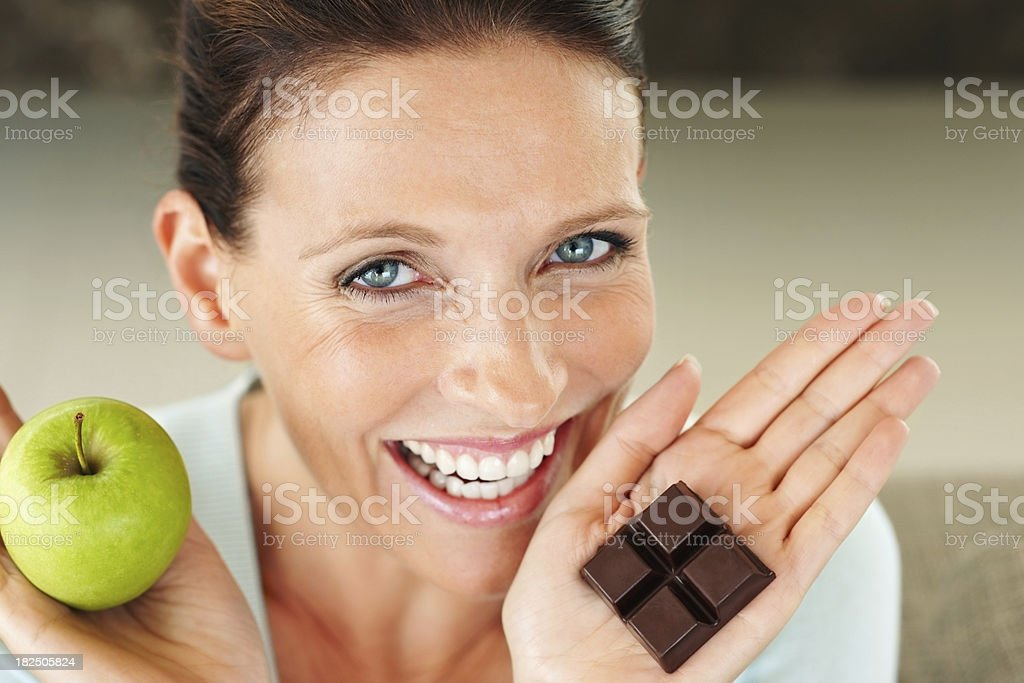 Smiling woman holding a piece of chocolate and an apple stock photo