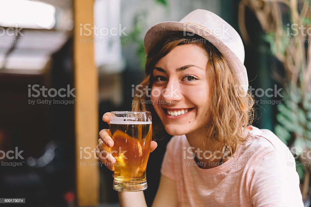 Lächelnde Frau hält einen Schoppen Bier – Foto