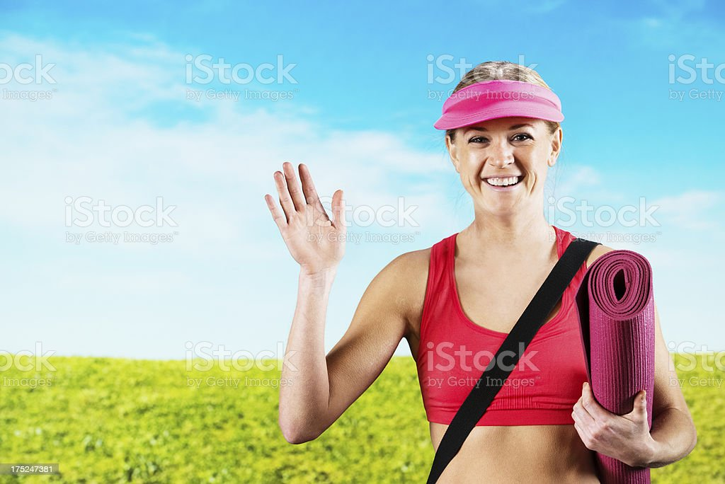 Smiling woman holding a yoga mat royalty-free stock photo