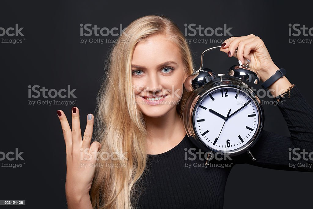 Smiling woman holding alarm clock and counting stock photo