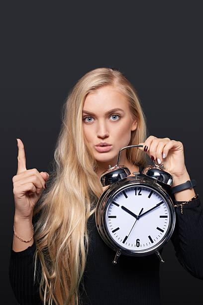 smiling woman holding alarm clock - markenuhren damen stock-fotos und bilder