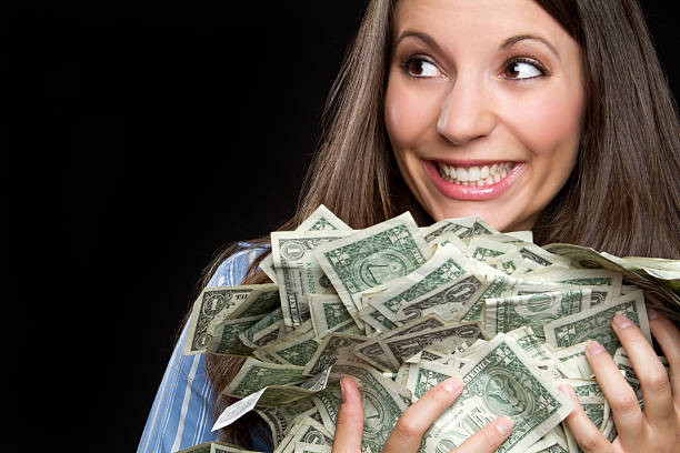 smiling woman holding armful of cash - money black background stock photos and pictures
