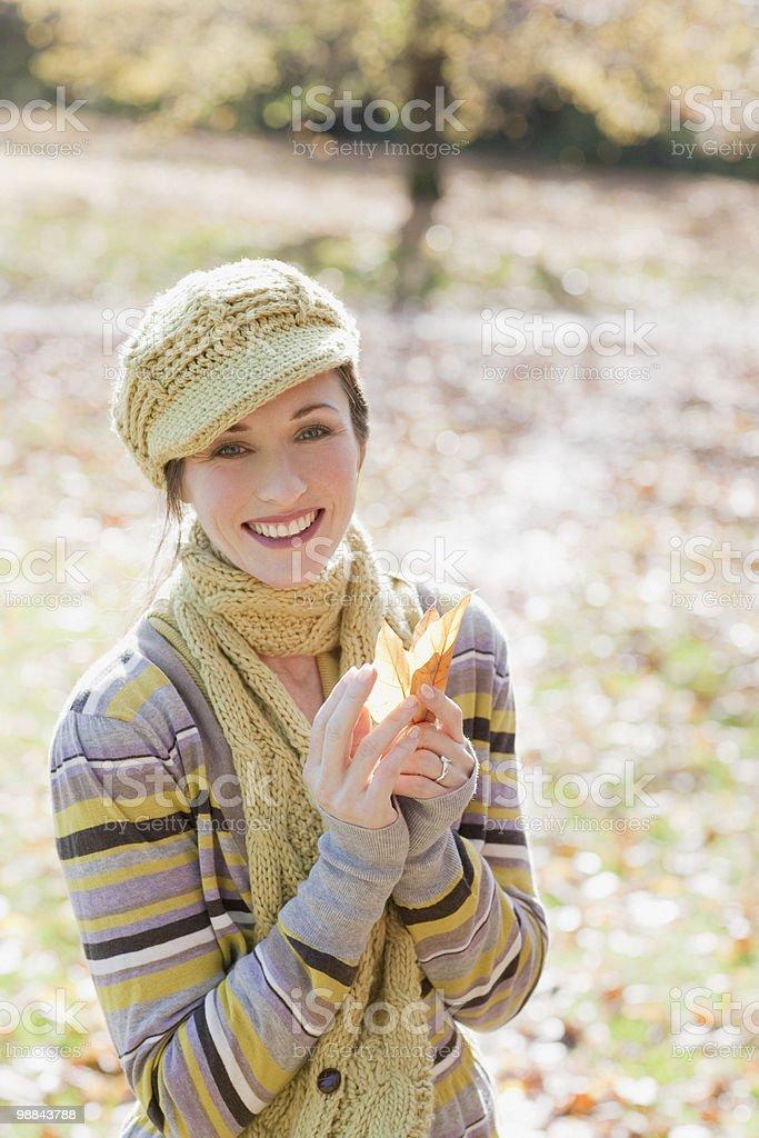 Sonriente mujer agarrando de otoño con hojas foto de stock libre de derechos