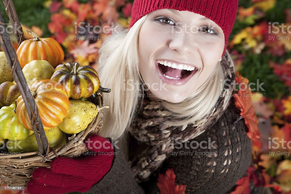 Smiling woman holding basket of pumpkins royalty-free stock photo