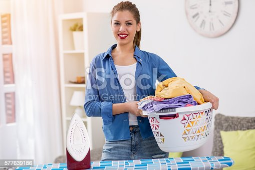 istock Smiling woman holding basket with clean clothes 577639186