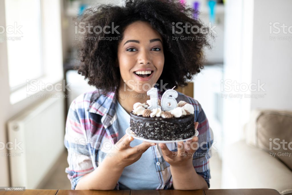 Mulher sorridente segurando o bolo de aniversário e cantando - foto de acervo