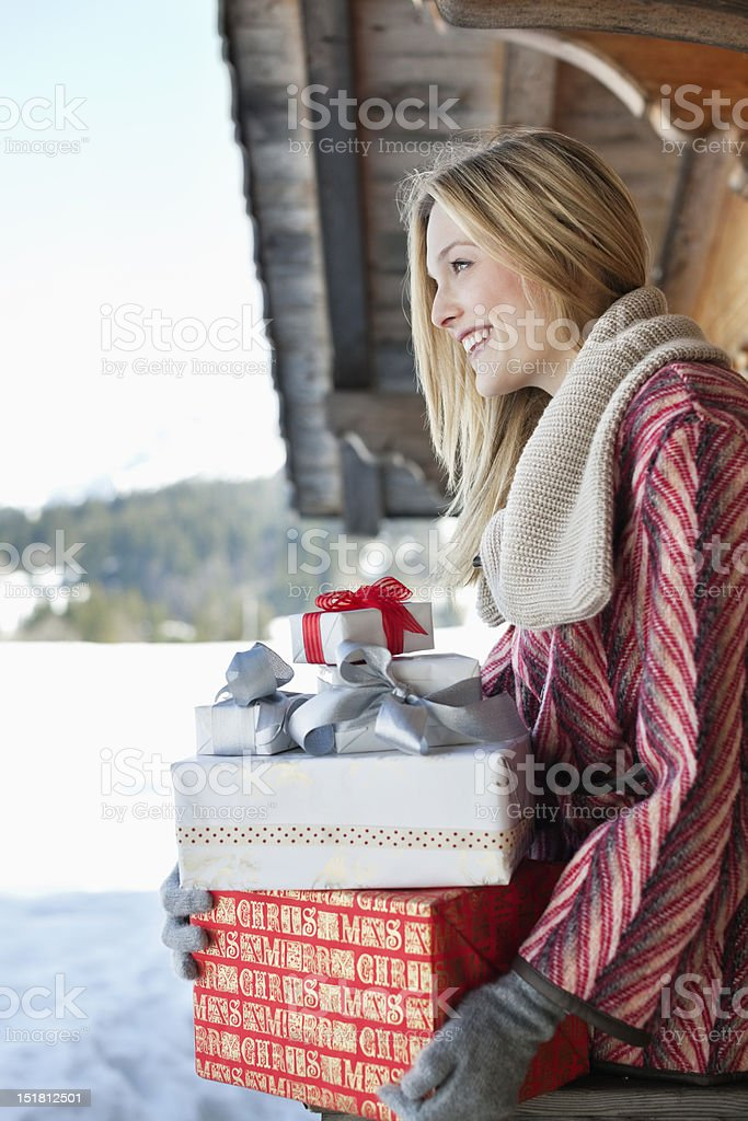 Smiling woman holding Christmas gifts on cabin porch stock photo