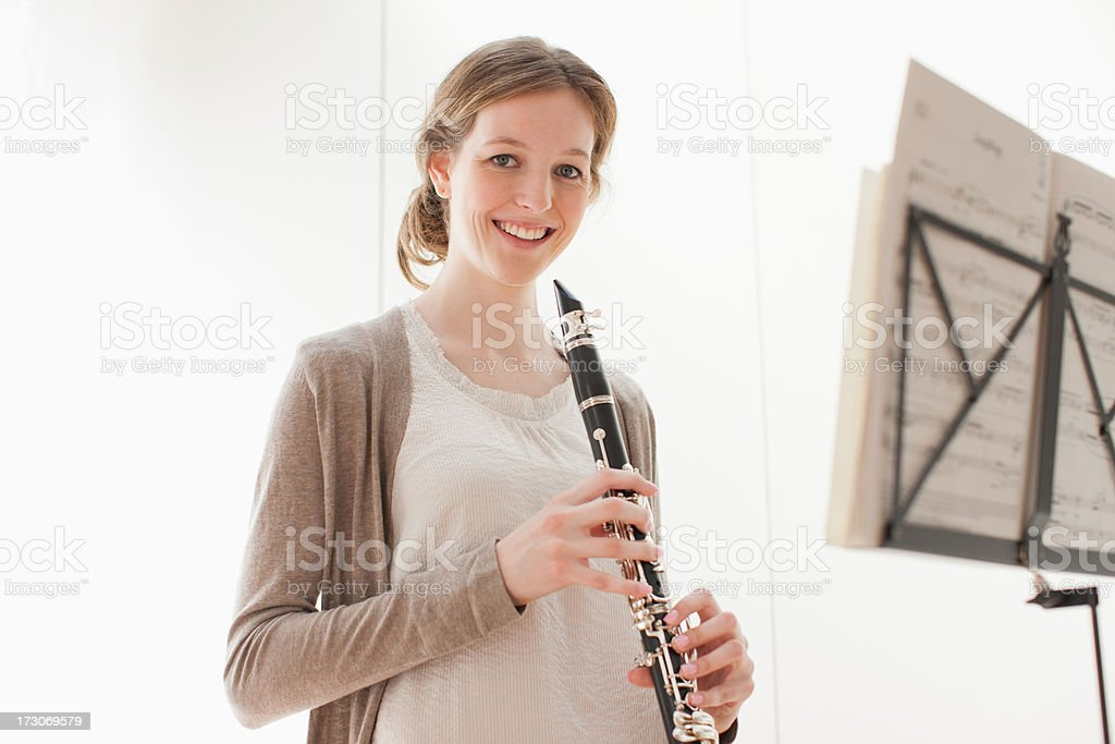 Smiling woman holding clarinet  royalty-free stock photo
