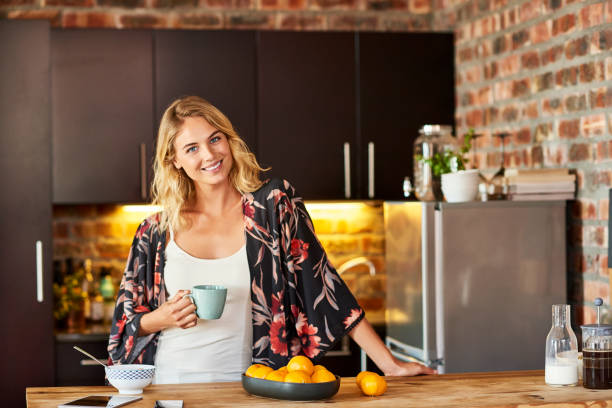 smiling woman holding coffee cup in kitchen - medium length hair stock photos and pictures