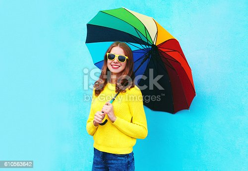 istock smiling woman holding colorful umbrella in autumn day over blue 610563642