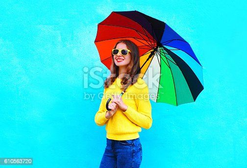 istock smiling woman holding colorful umbrella in autumn day over blue 610563720