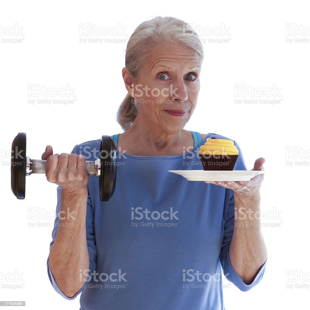Smiling Woman Holding Dumbbell and Cupcake stock photo