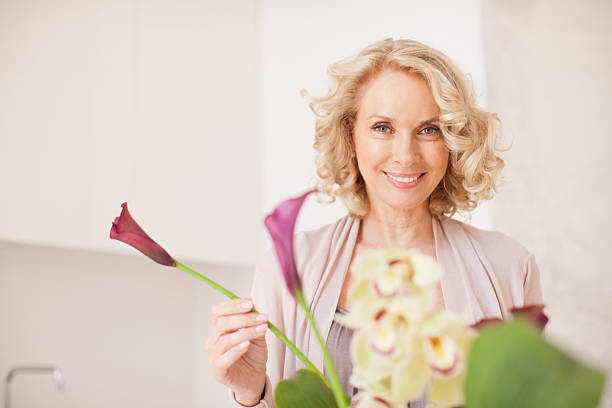 smiling woman holding flowers - arranging stock photos and pictures