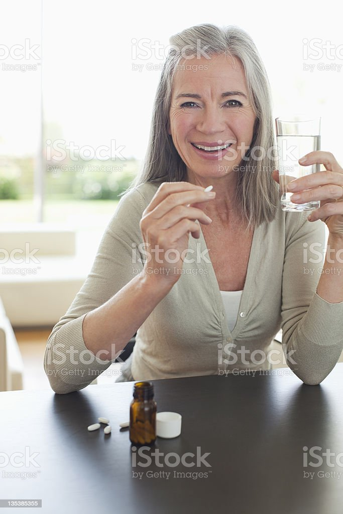 Smiling woman holding glass of water and taking pills stock photo