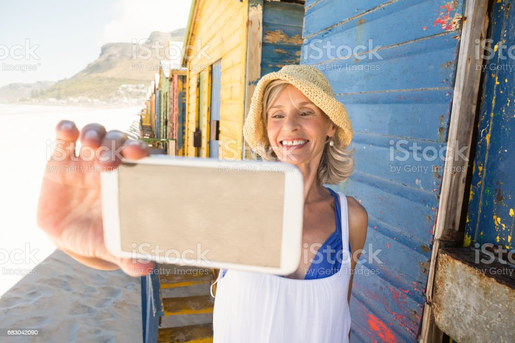 Smiling woman holding phone while standing against wall foto de stock royalty-free