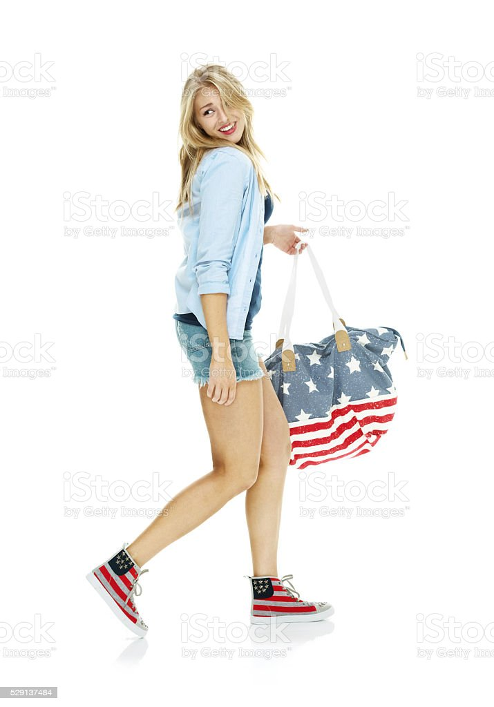 Smiling woman holding purse and walking stock photo