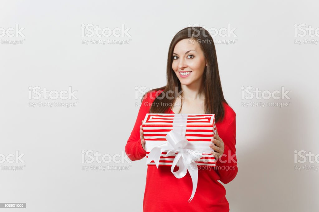 Smiling woman holding red striped present box with ribbon, bow isolated on white background. For advertisement. St. Valentine's Day, International Women's Day, Christmas, birthday, holiday concept. stock photo