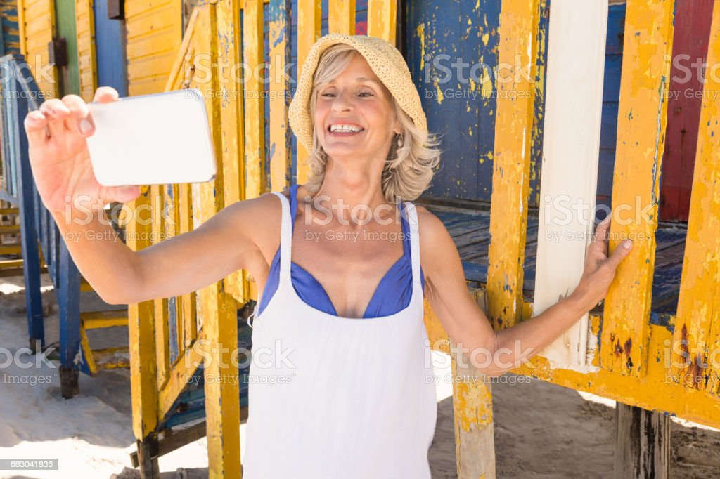 Smiling woman holding smart phone while standing against wall foto de stock royalty-free