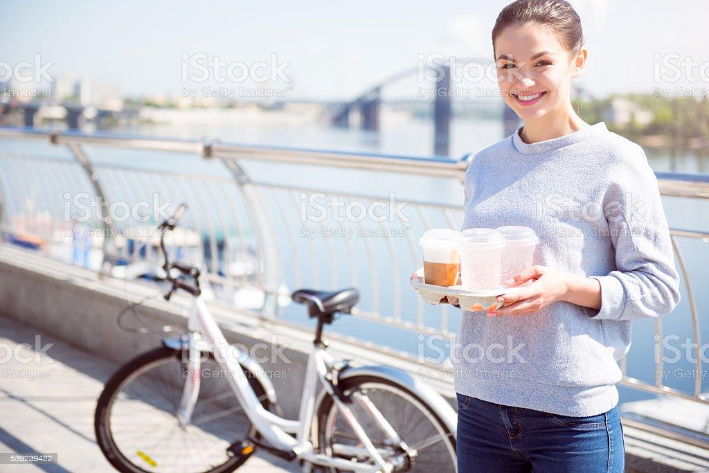 Sonriente mujer sosteniendo algunas bebidas foto de stock libre de derechos