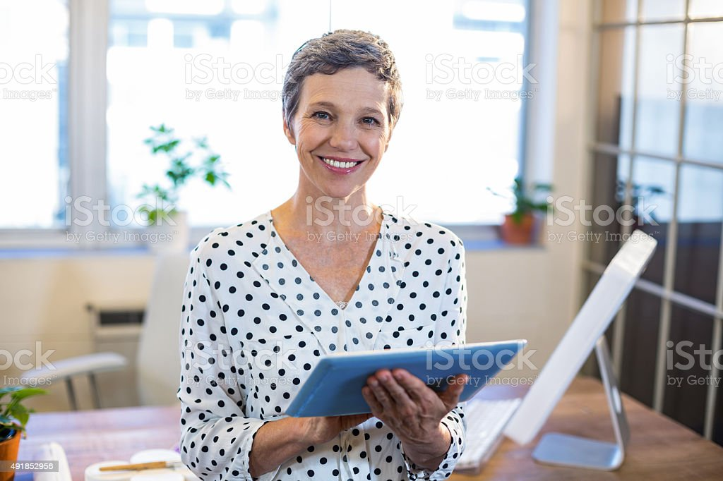 Smiling woman holding tablet and looking at camera stock photo