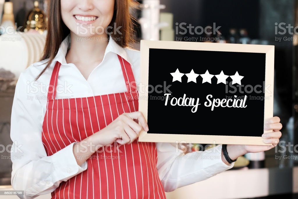 Smiling woman holding Today's special and five start board sign over blur cafe background, food and drinks recommended concept stock photo