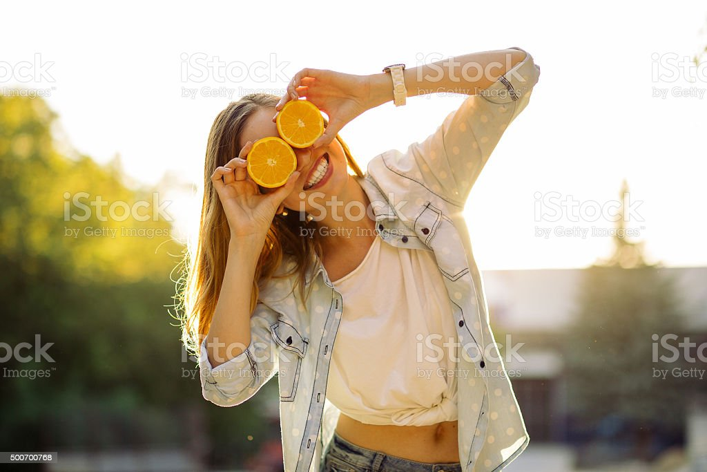 Smiling woman holding two orange in hands stock photo