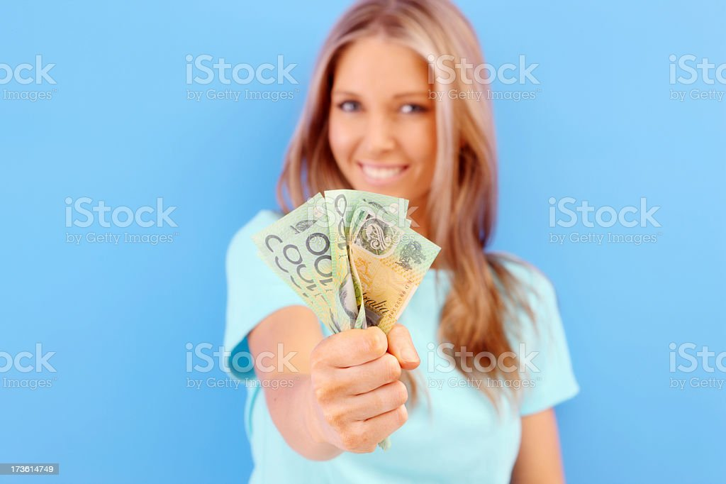 Smiling woman holding up Australian money stock photo