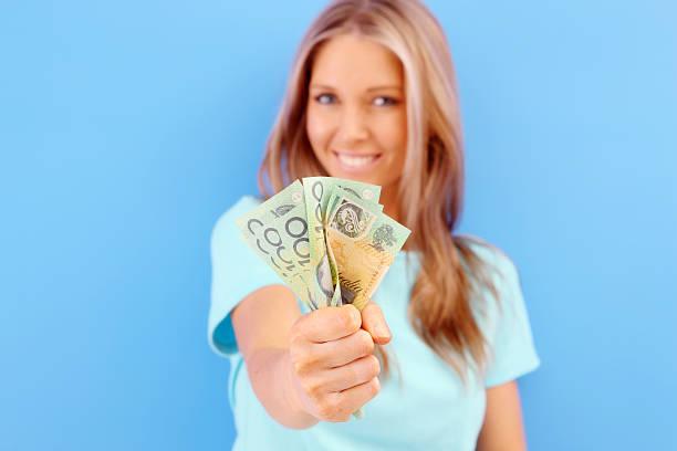 Smiling woman holding up Australian money stock photo