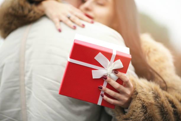 バレンタイン ギフトを押しながら男を抱いて笑顔の女性 - ガールフレンド ストックフォトと画像