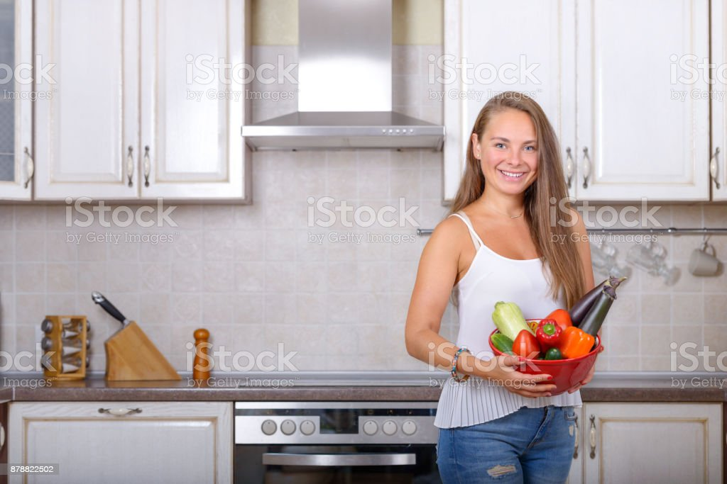 Smiling woman holds in hands bowl with vegetable stock photo