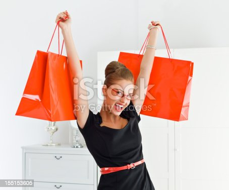 Portrait of excited young adult woman holding up red shopping bags in both hands. Looking at camera and smiling.