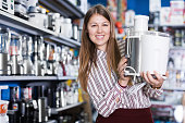 Smiling woman housewife looking  kitchen machine in household appliances shop