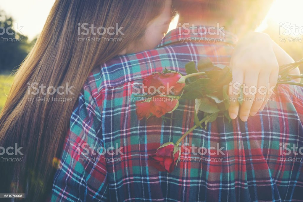 Smiling woman hugging her boyfriend and holding the rose she got for Valentine's Day. royalty-free stock photo
