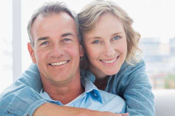 lachende vrouw haar echtgenoot knuffelen op de bank van achteren - 50 54 jaar stockfoto's en -beelden