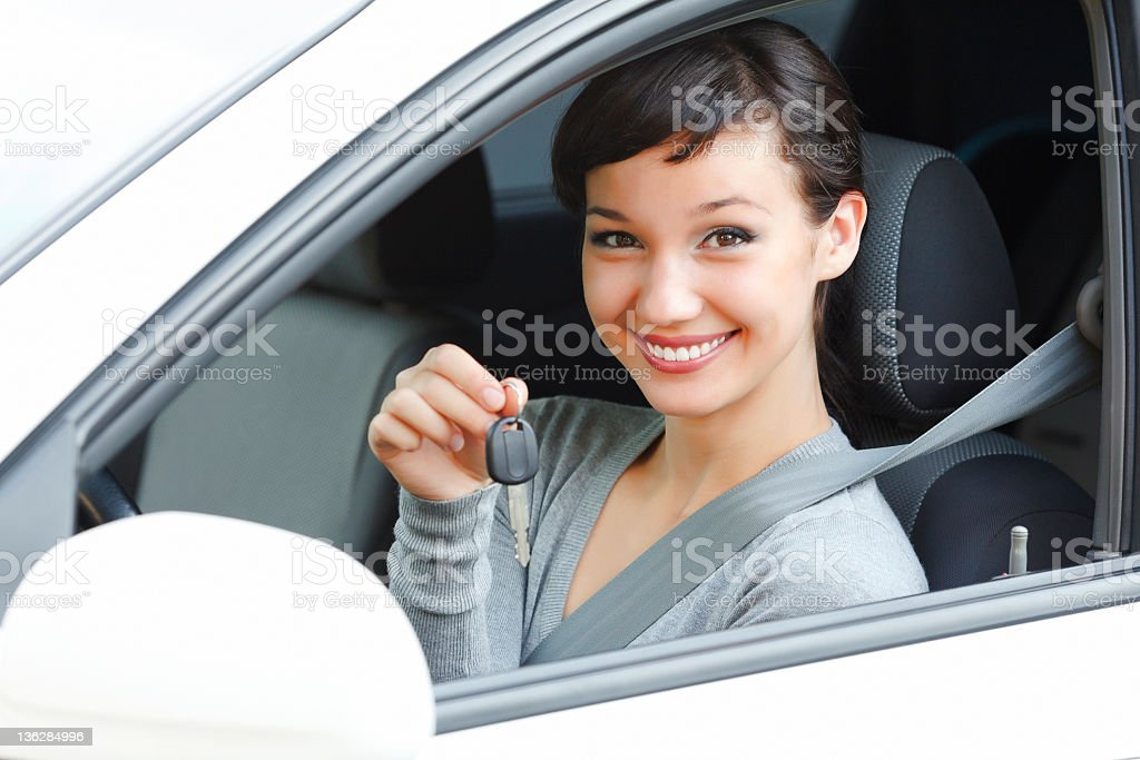 A smiling woman in a drivers seat of a car holding keys stock photo