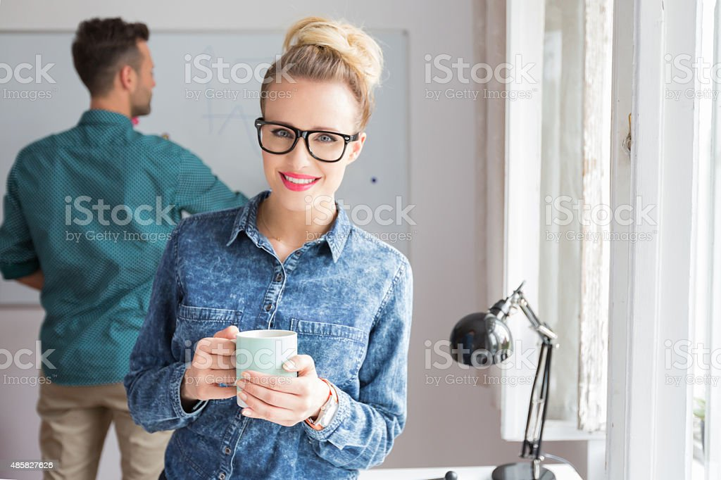Smiling woman in an office with cup of coffee Blonde woman wearing jeans shirt and nerd glasses standing in an office, holding cup of coffee and smiling at camera. Man drawing on the board in the background. Adult Stock Photo