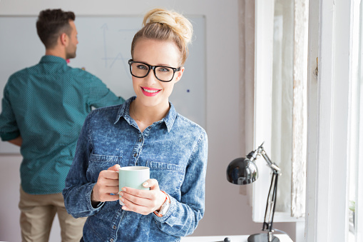 Smiling Woman In An Office With Cup Of Coffee Stock Photo - Download Image Now