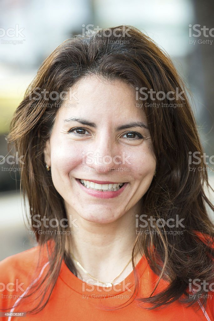 Smiling woman in an orange shirt looking at camera. stock photo