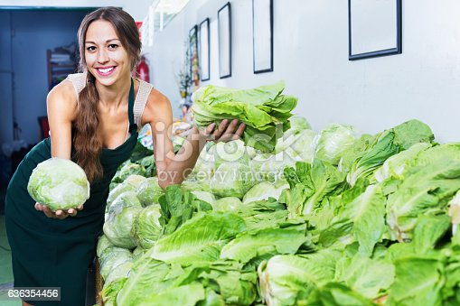 istock Smiling woman in apron selling fresh lettuce 636354456
