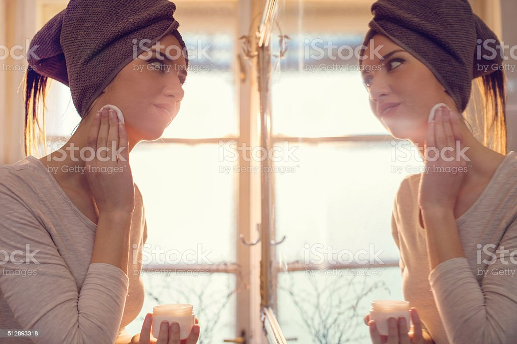 Smiling woman in bathroom cleaning her face. stock photo