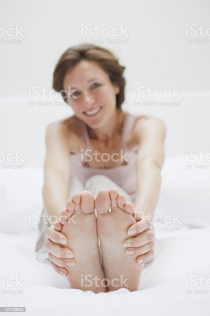 Smiling woman in bed holding feet royalty-free stock photo