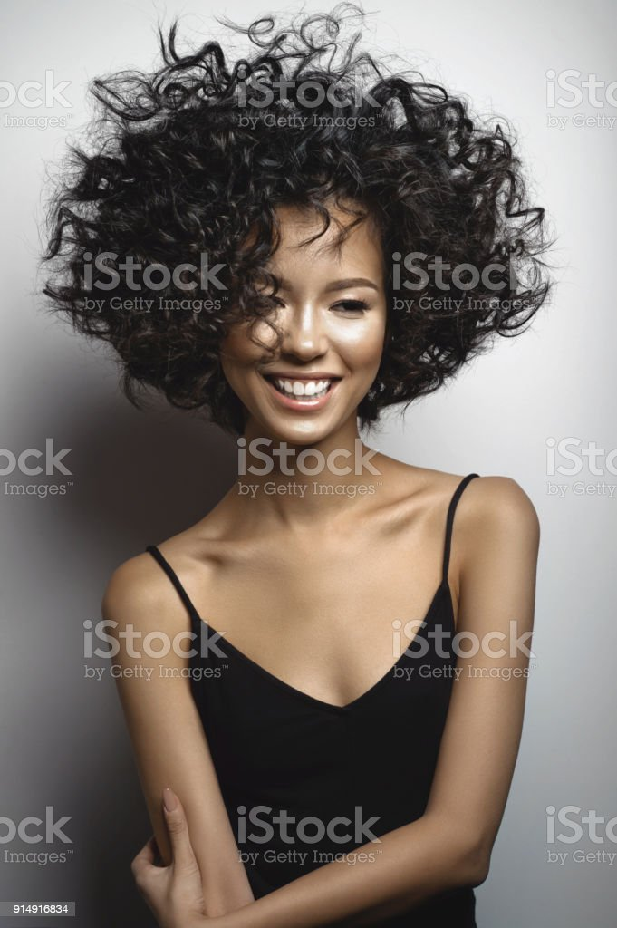 Smiling woman in black dress with afro curls hairstyle stock photo
