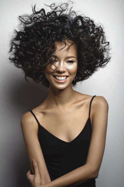 Lächelnde Frau in schwarzem Kleid mit Afro locken Frisur – Foto