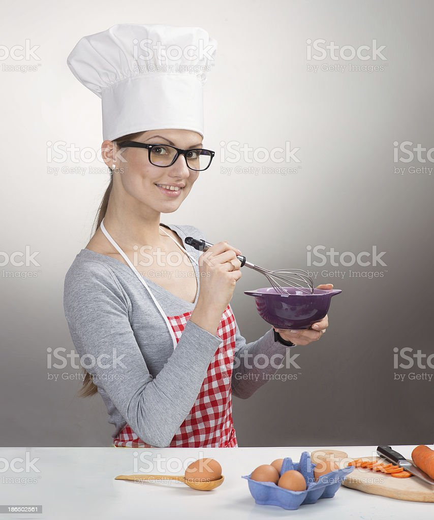 Smiling woman in chef's hat whisking eggs royalty-free stock photo