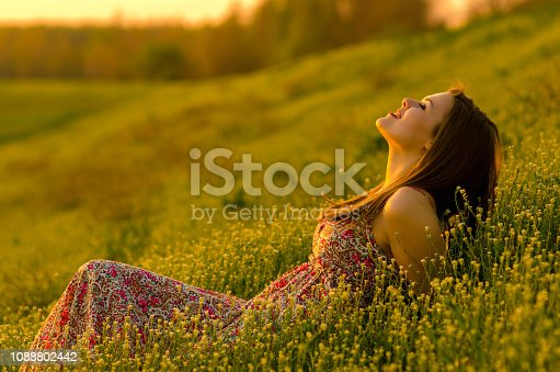Beautiful young woman in dress lying on the meadow on a sunny summer day.
