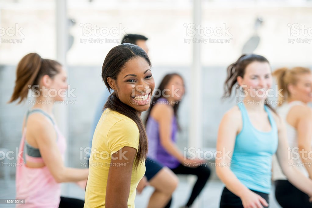 A multi-ethnic group of young adults are doing an aerobic exercise...