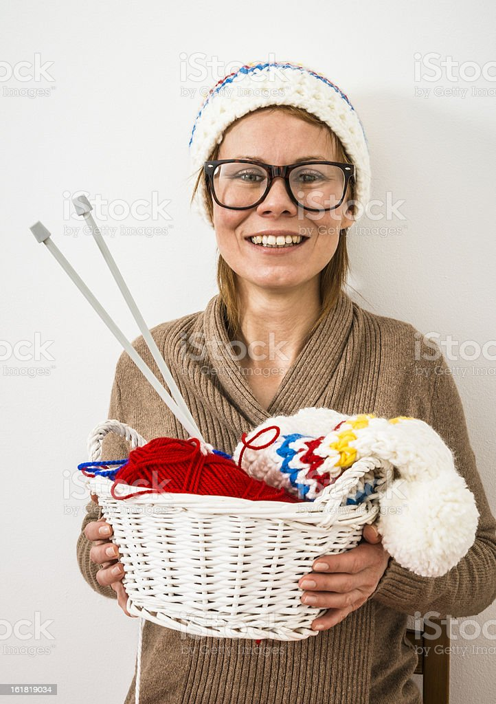Smiling woman in glasses sitting on chair, knitting winter caps royalty-free stock photo
